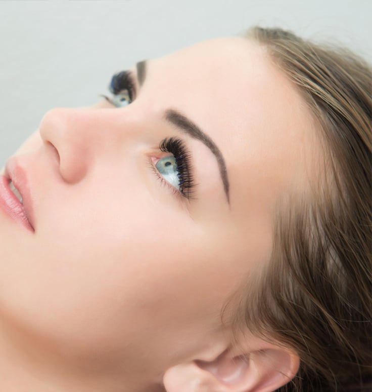 a side view of a beautiful woman with russian volume eyelash extensions