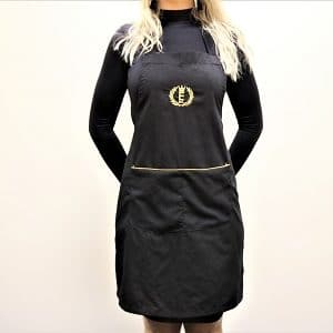 woman wearing a full size black apron with gold trim on the pockets and an Enchanted logo symbol embrodiered in gold in the top centre