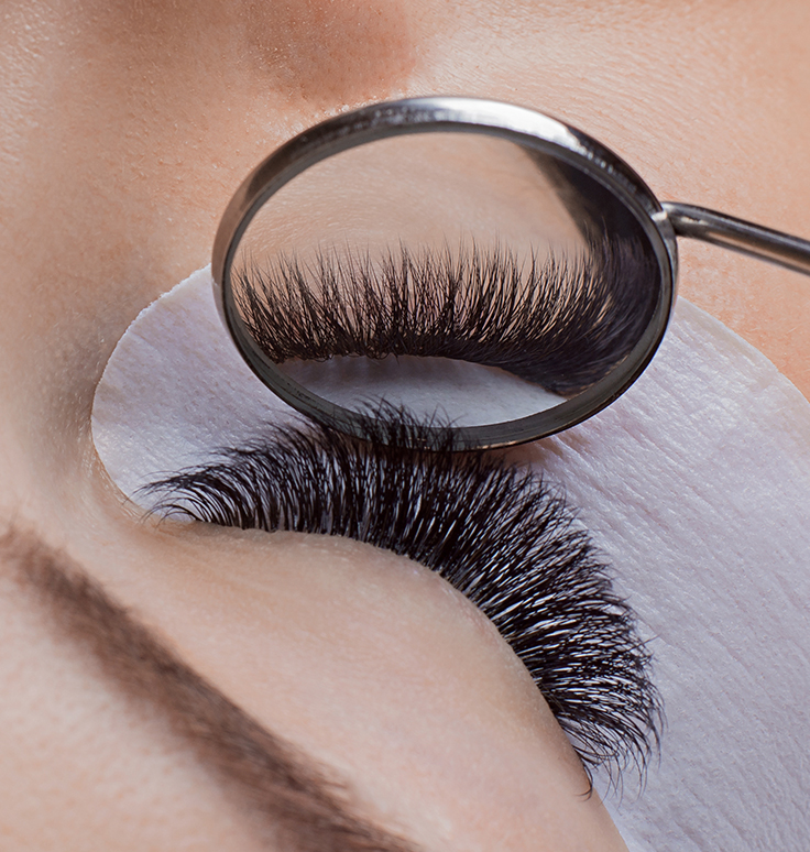 small dental mirror reflection of volume eyelash extensions application in a closed eye demonstrating techniques from our classic to volume lash extension training courses