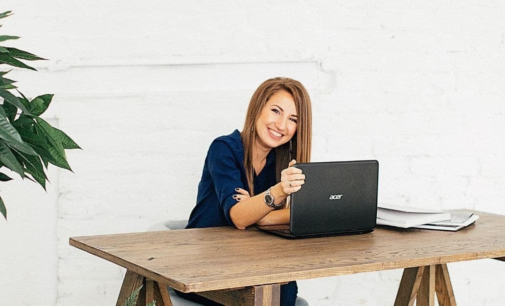 young woman working on her laptop setting up her business for success